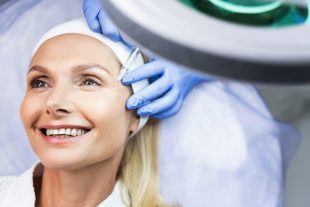 High-spirited female patient in a headband enjoying her skin rejuvenating procedure in a beauty parlor